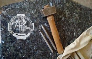 logo du concours un des meilleurs ouvrier de france en taille de pierre gravé sur du granite
